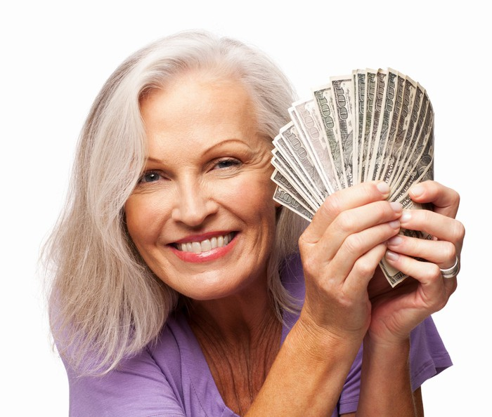 Smiling older woman holding fan of hundred dollar bills