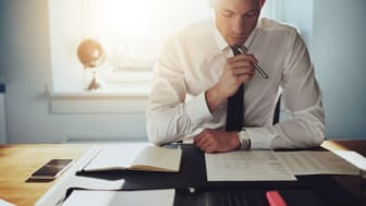 picture of well-dressed man at desk studying financial reports