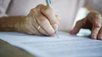 A person signs some documents.