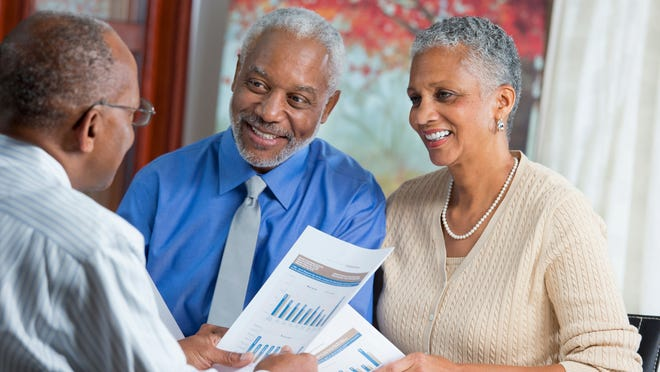 Older couple talking with financial advisor.