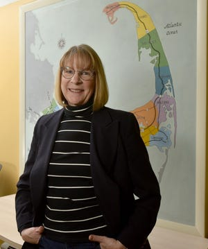 Wendy Northcross, CEO of the Cape Cod Chamber of Commerce, stands in front of a vintage Cape Cod map outside her office at the chamber's headquarters off Route 6 in Centerville. Northcross announced her retirement Monday after 24 years at the chamber's helm.