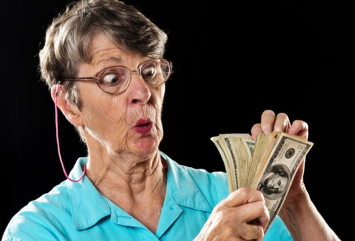 An older woman is looking surprised and amazed as she counts her cash.