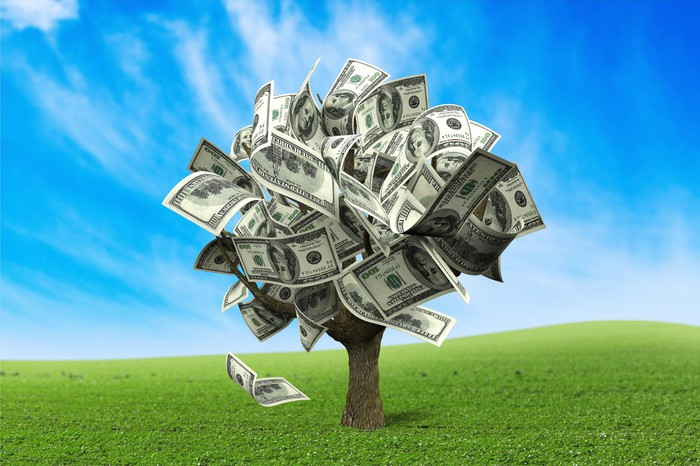 A tree made of money stands in a green field.
