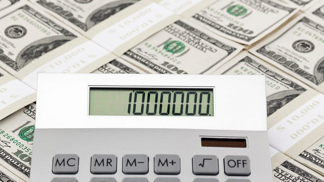 Stacks of cash with a calculator reading 1 million, to represent retiring a millionaire.