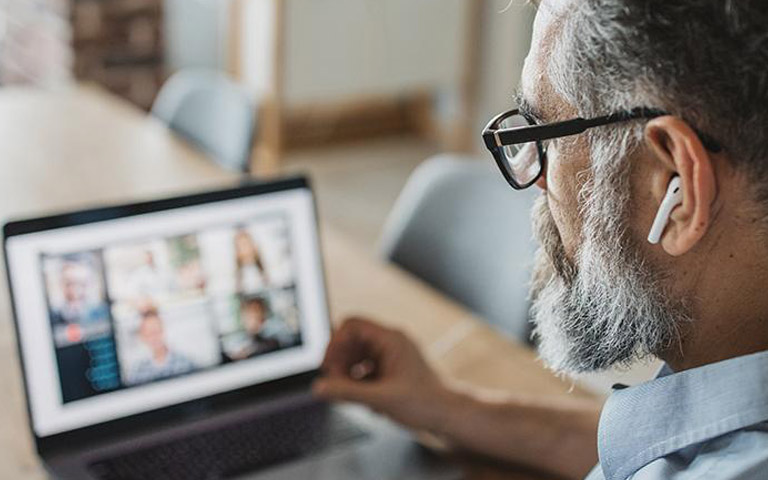 Gray-hair man with earbuds looking at a computer during online meetings