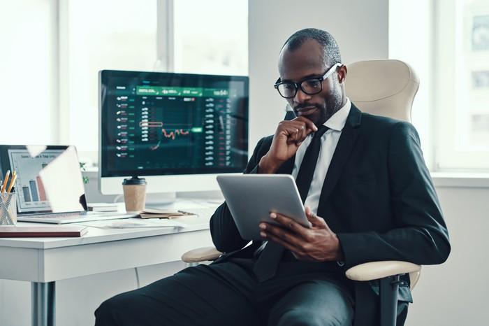 Investor looking at computer and charts.