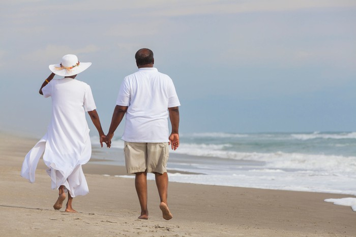 Couple holding hands walking down a beach.