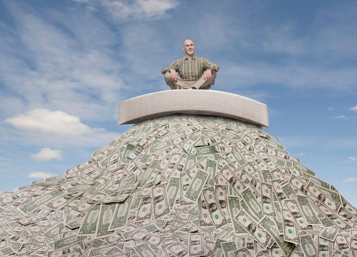 Senior man sitting atop a rising pile of money.