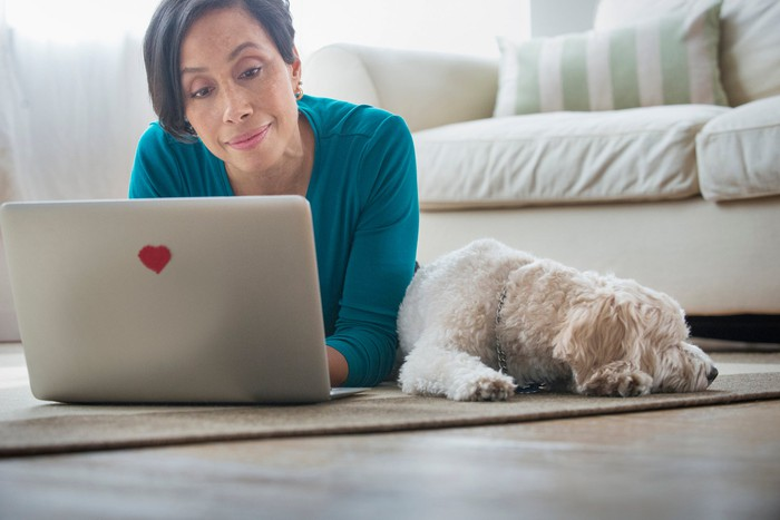 Older woman types on laptop on floor while dog rests next to her