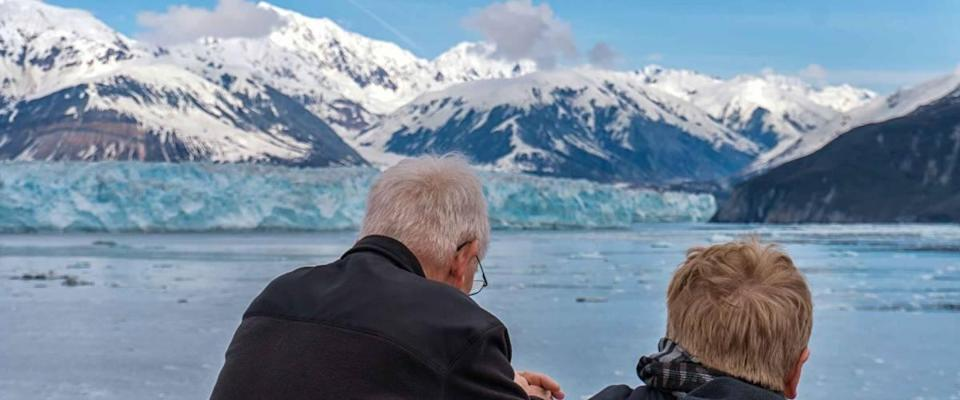 Old couple on a cruise ship in Alaska. Husband and wife are enjoying an amazing view of Hubbard Glacier and iceberg. Snow peaks and ice all around in the sea.