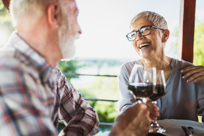 Smiling older man and woman clinking wine glasses