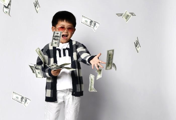 A kid throwing money around.