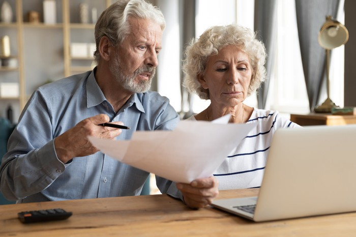 Older man holds documents and sits next to older woman at laptop