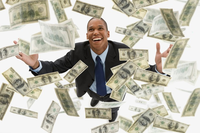 Smiling man with money falling all around him.