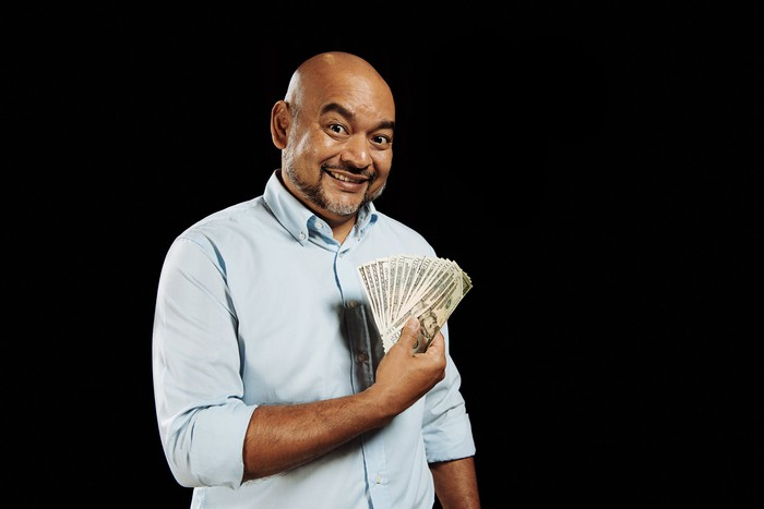 A man is holding cash fanned out and looking pleased.
