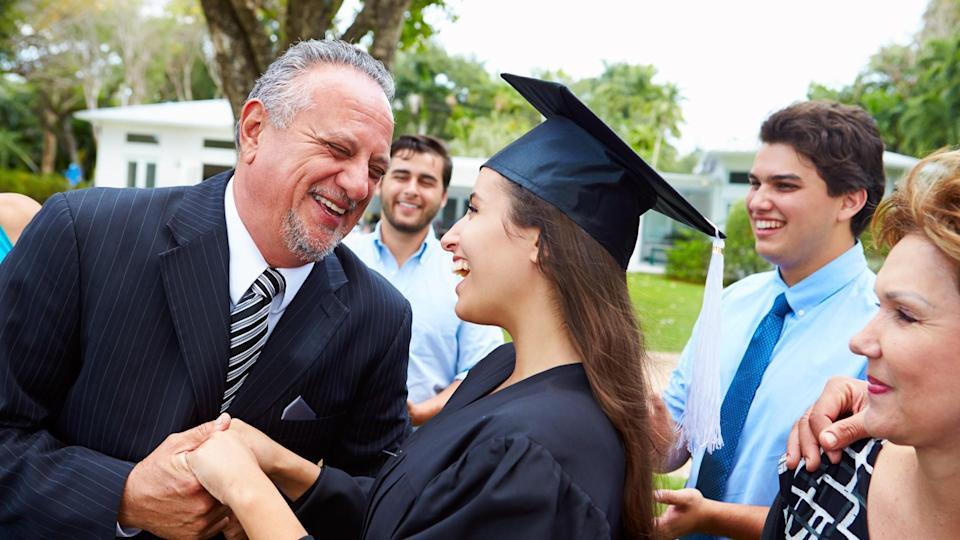 Hispanic Student And Family Celebrating Graduation Smiling.