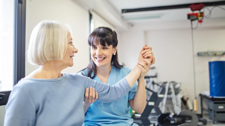 Nurse assisting senior woman with hand exercise.