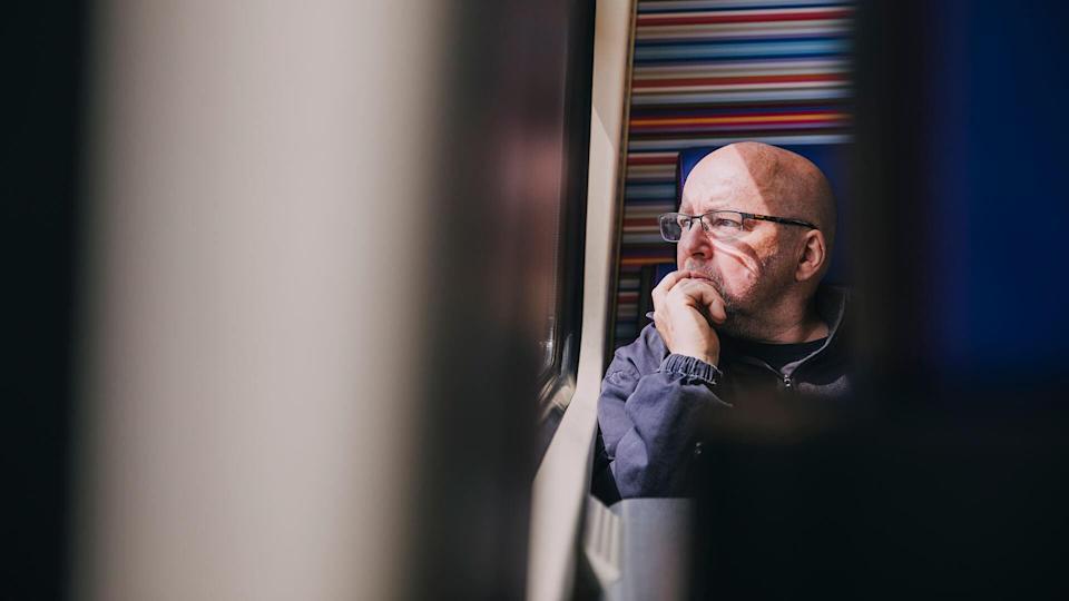 An older man sitting alone on a train in Amsterdam.