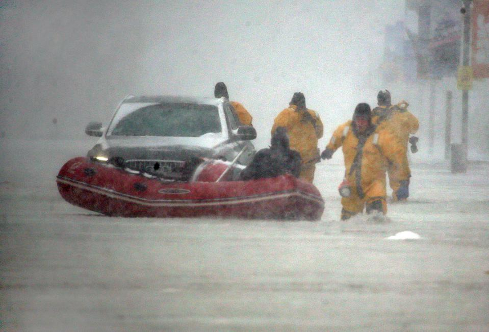 (010418 Boston, MA) Justin Plaza, at right, with Boston Fire Rescue pulls an inflatable boat as he and other firefighters save a man from his flooded car on Commercial Wharf during the storm on Thursday,January 4, 2018. Staff Photo by Nancy Lane