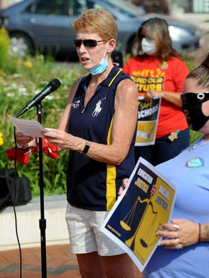 Framingham Teachers Association President Christine Mulroney speaks at a rally in front of City Hall Wednesday afternoon to speak out against proposed state budget cuts.