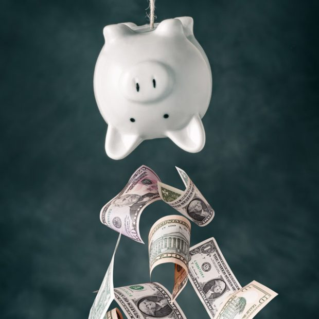 Retirement money falling out of a piggy bank.
