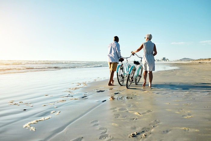 retired couple enjoying the view with bikes on the beach.