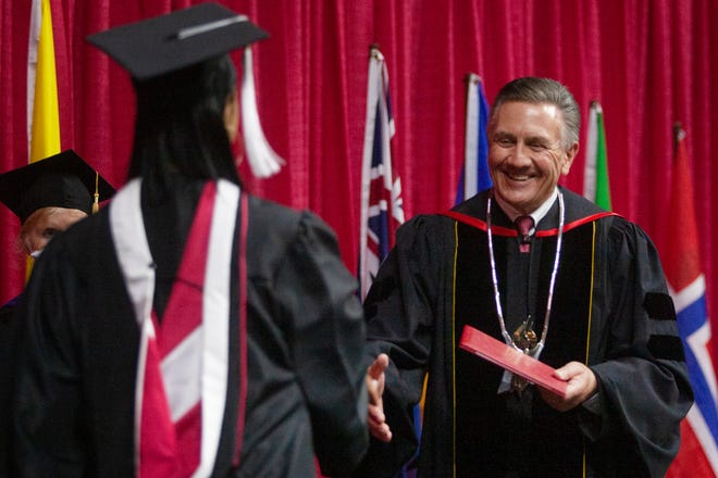 Grand View University President Kent Henning smiles as he shakes hands with 2021 graduates during commencement Monday, April 26, 2021 at Wells Fargo Arena. It was the 22nd commencement for Henning as Grand View president.