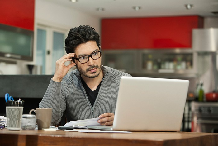 Person with serious expression at laptop.