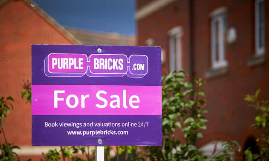 A Purple Bricks estate agents for sale sign outside a house on a modern housing estate