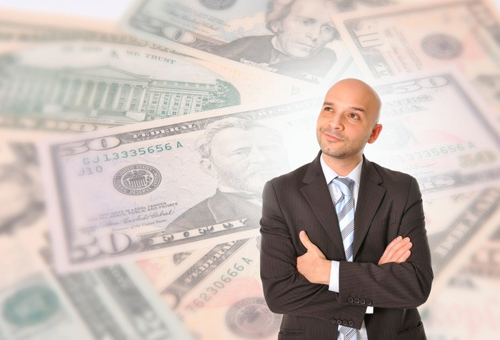 A person is looking wistful, against a background of cash.